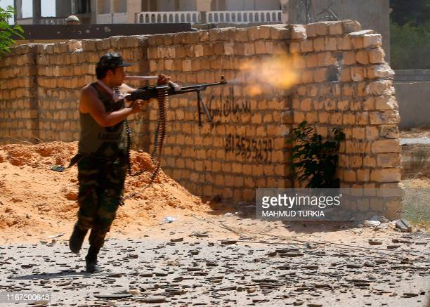 TOPSHOT A fighter loyal to the internationally recognised Libyan Government of National Accord fires his gun during clashes with forces loyal to...