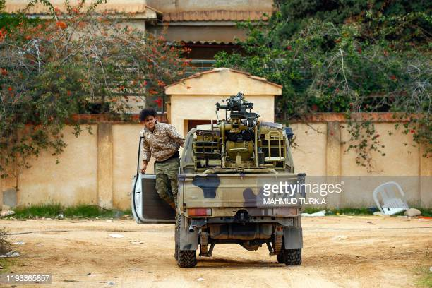 Fighter loyal to the internationally recognised Libyan Government of National Accord exits a vehicle in an area south of the Libyan capital Tripoli...
