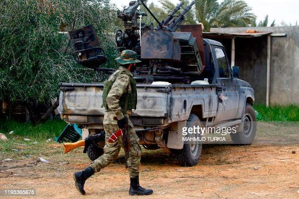 A fighter loyal to the internationally recognised Libyan Government of National Accord walks past a vehicle in an area south of the Libyan capital...