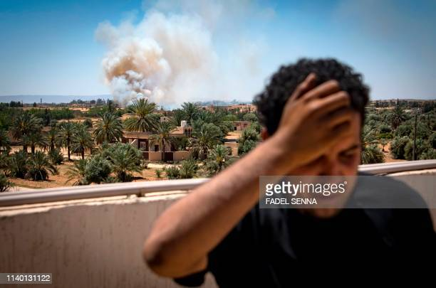 Fighter loyal to the internationally-recognised Government of National Accord stands on a rooftop as smoke rises in the distance during clashes with...