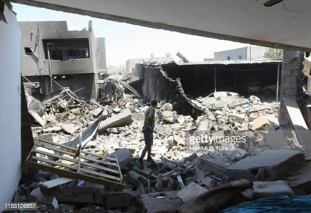 Fighter loyal to the Libyan Government of National Accord forces checks a building near the the Yarmouk military compound, south of the Libyan...