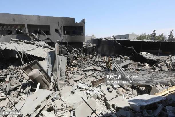Fighter loyal to the Libyan Government of National Accord forces gestures among the ruins of a building near the the Yarmouk military compound,...