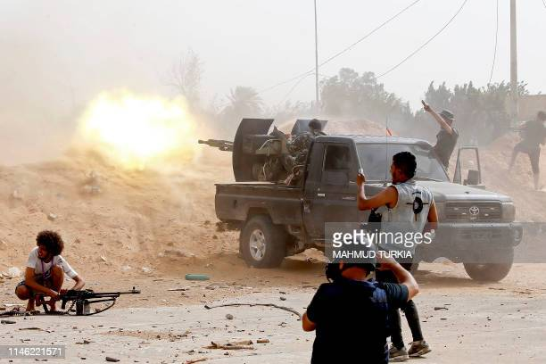 TOPSHOT A fighter loyal to the Libyan internationallyrecognised Government of National Accord fires a heavy machine gun as a press photographer take...