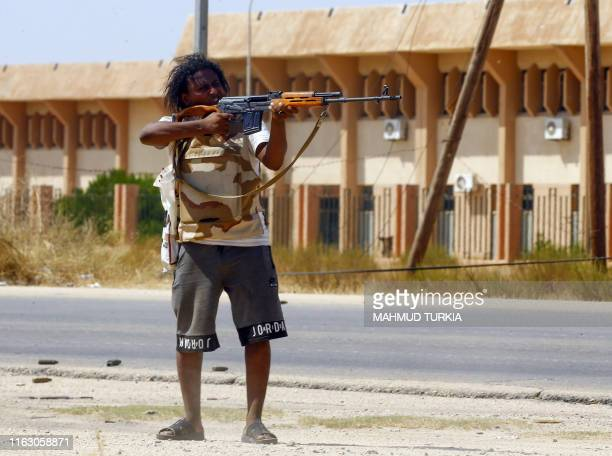 TOPSHOT A fighter loyal to the UNrecognised Government of National Accord points his gun toward enemy lines during clashes with forces loyal to...