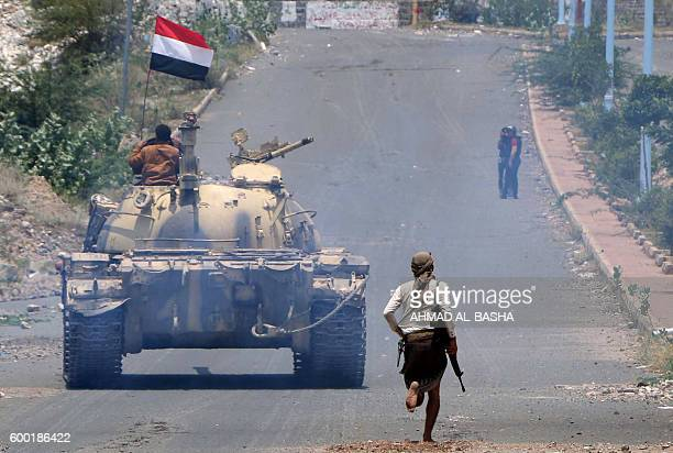 A fighter loyal to Yemen's exiled President Abedrabbo Mansour Hadi runs behind a tank flying the Yemeni flag near the country's thirdlargest city of...