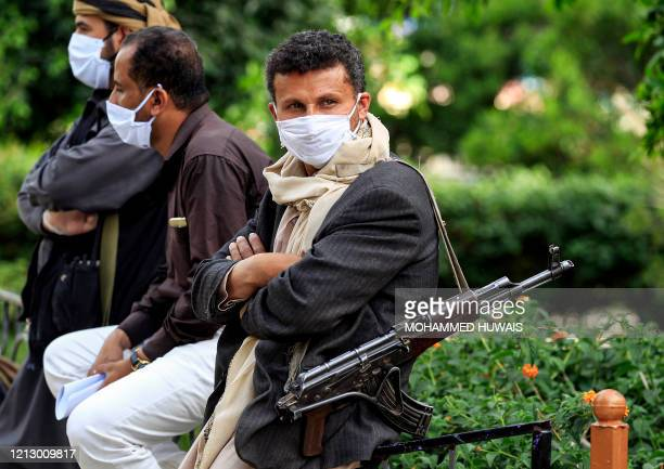 TOPSHOT A fighter loyal to Yemen's Huthi rebels acting as security looks on while wearing a face mask and latex gloves and slinging a Kalashnikov...