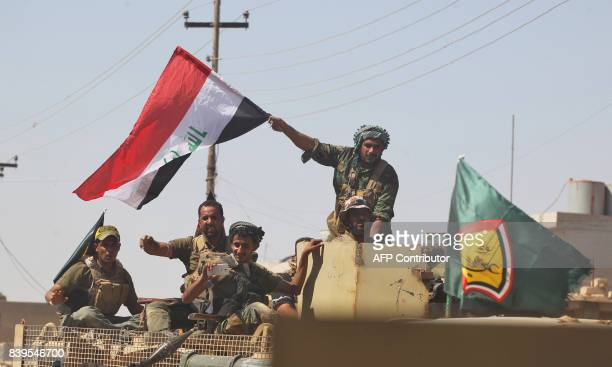 A fighter of Hashed AlShaabi waves an Iraqi flag as others use a cell phone to take a selfie from the turret of an armoured vehicle during the...