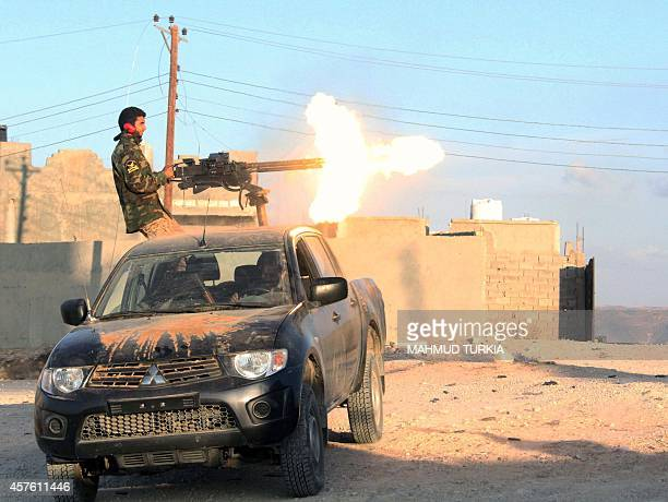 A fighter of Libya's Fajr Libya group fires his gun during clashes in the hill village of Kikla southwest of Tripoli on October 21 2014 The...