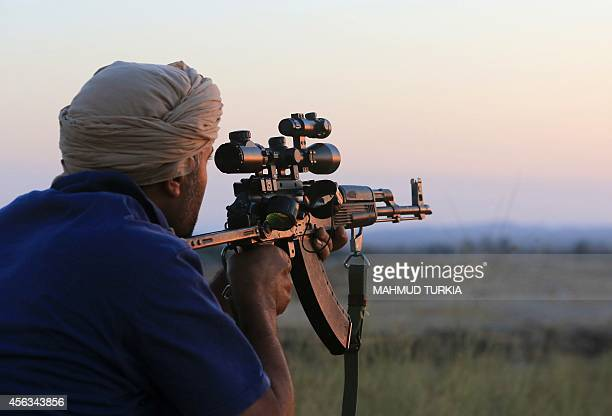 A fighter of Libya's Fajr Libya militia watches as he keeps a position his group took from a rival militia in the southern part of the town of...