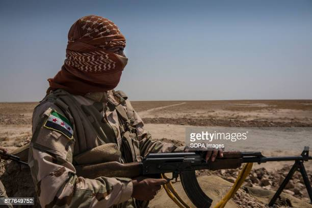 A fighter of Quwat Al Nukhba looks towards the village of Islamic State only a kilometre away from their position