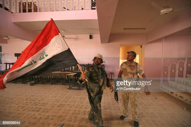 A fighter of the Hashed AlShaabi carries an Iraqi flag as he walks through a building in the town of Tal Afar west of Mosul after the Iraqi...