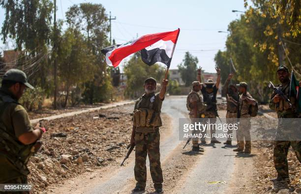 A fighter of the Hashed AlShaabi waves an Iraqi flag as others behind flash the victory gesture during the advance through the town of Tal Afar west...