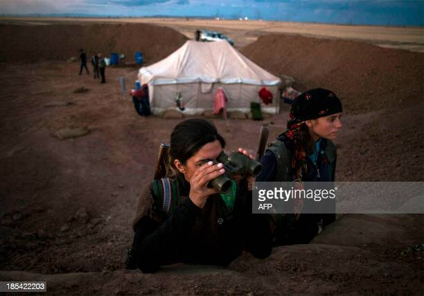 A fighter of the Kurdish of the Committees for the Protection of the Kurdish People looks through binoculars behind a fortified wall as she looks for...