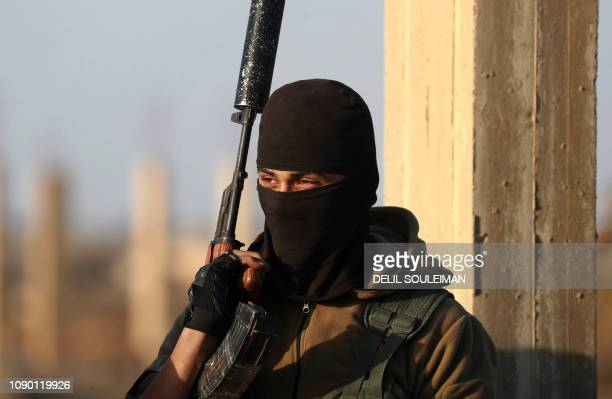 A fighter of the Syrian Democratic Forces keeps watch in the Syrian village of Baghuz in the countryside of the eastern Deir Ezzor province on...