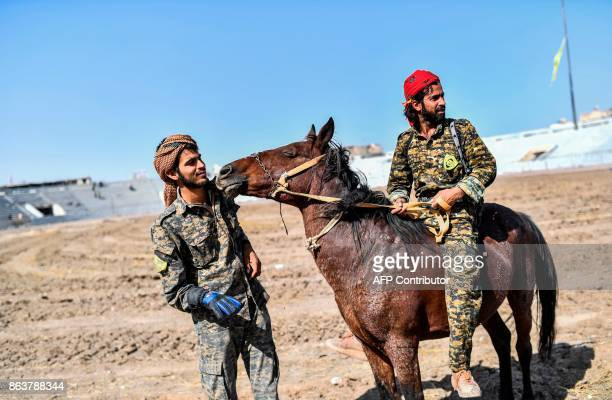 A fighter of the Syrian Democratic Forces rides a horse at the stadium in Raqa on October 20 as he celebrates with his comrades after they retook the...