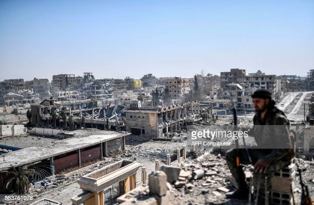 A fighter of the Syrian Democratic Forces sits on guard on a rooftop in Raqa on October 20 after retaking the city from Islamic State group fighters...