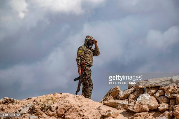 A fighter of the Syrian Democratic Forces stands at a position close to the camp of Baghouz where remaining Islamic State group fighters and their...