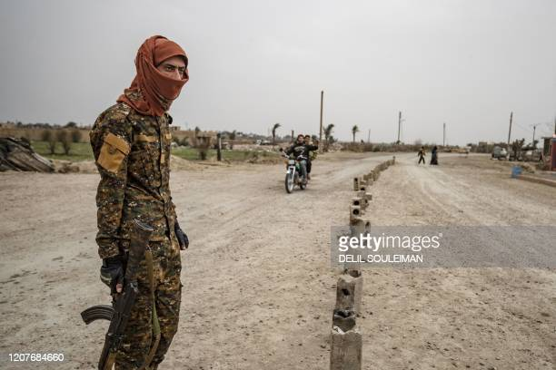 TOPSHOT A fighter of the Syrian Democratic forces stands guard at the entrance of the eastern Syrian village of Baghouz on March 13 a year after the...