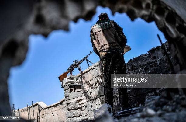 A fighter of the Syrian Democratic Forces stands guard on a rooftop in Raqa on October 20 after retaking the city from Islamic State group fighters...