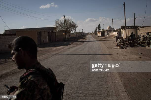 A fighter of the Syrian Democratic Forces stands in an an empty street in the western neighborhood of Jazrah on the outskirts of Raqqa on October 30...