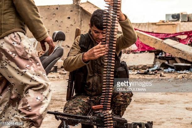 TOPSHOT A fighter of the USbacked Syrian Democratic Forces loads an ammunition belt at a position in the village of Baghouz near Syria's border with...