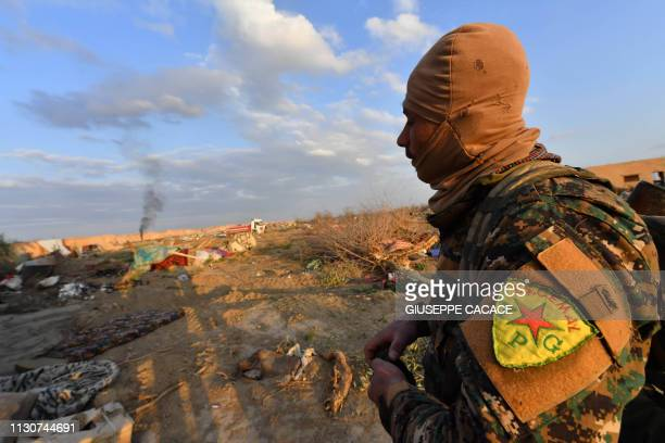 A fighter of the USbacked Syrian Democratic Forces looks on at the remains of an Islamic State group jihadists' camp near the village of Baghouz in...