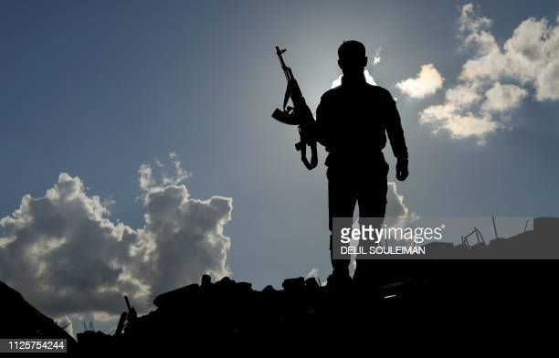 TOPSHOT A fighter of the USbacked Syrian Democratic Forces stands guard in the frontline Syrian village of Baghouz on February 18 2018 SDF forces...