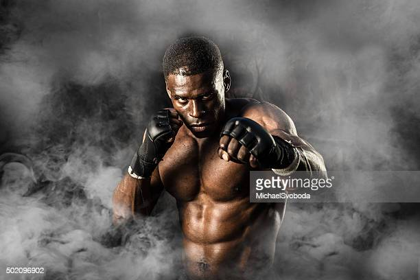 mma fighter on a smokey  background - mixed martial arts stockfoto's en -beelden