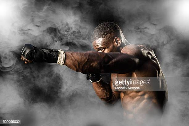 mma fighter on a smokey  background - mixed martial arts stock pictures, royalty-free photos & images
