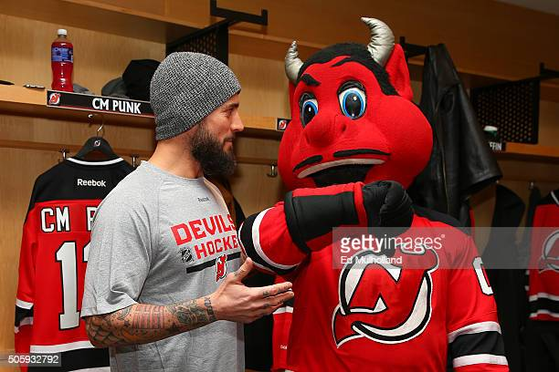 UFC fighter Phil 'CM Punk' Brooks jokes around with New Jersey Devils mascot 'NJ' before their workout at the Amerihealth Pavilion on January 20 2016...
