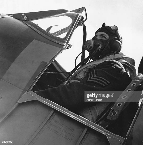 Fighter pilot sitting in the cockpit of his Spitfire after returning from a battle with enemy aircraft, July 1940.
