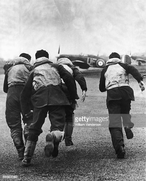 Fighter pilots of No 601 Squadron RAF Squadron running to their Hawker Hurricane aircraft during the Blitz 9th January 1941