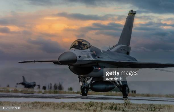 aereo da caccia f-16 pronto a deflusso in pista al tramonto - base militare foto e immagini stock