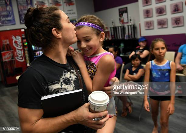 Fighter Sara McMann the 2004 Olympic women's freestyle wrestling silver medalist kisses her daughter Bella Goodale after she mastered a new...