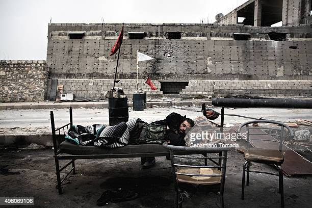 FSA fighter sleeps along the road connecting the liberated side of Aleppo and the one held by the regime March 12 2013