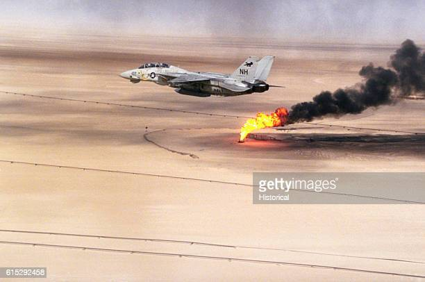 A Fighter Squadron 114 F14A Tomcat aircraft flies over an oil well still burning in the aftermath of Operation Desert Storm