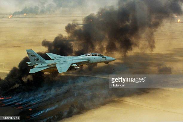 A Fighter Squadron 114 F14A Tomcat aircraft flies over oil well fires still burning in the aftermath of Operation Desert Storm August 1991
