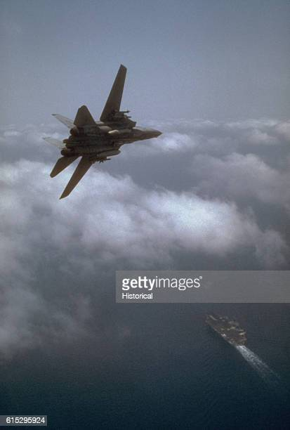 A Fighter Squadron 32 F14A Tomcat aircraft banks toward the aircraft carrier USS John F Kennedy The Kennedy and its embarked air wing are in the Red...
