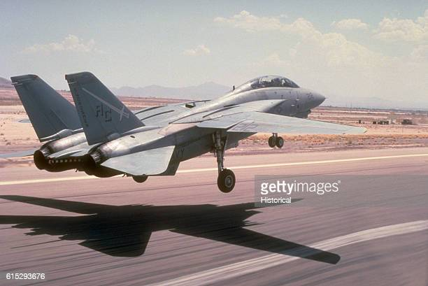 A Fighter Squadron 32 F14A Tomcat aircraft lands at a desert airfield during Operation Desert Shield VF32 is based aboard the aircraft carrier USS...