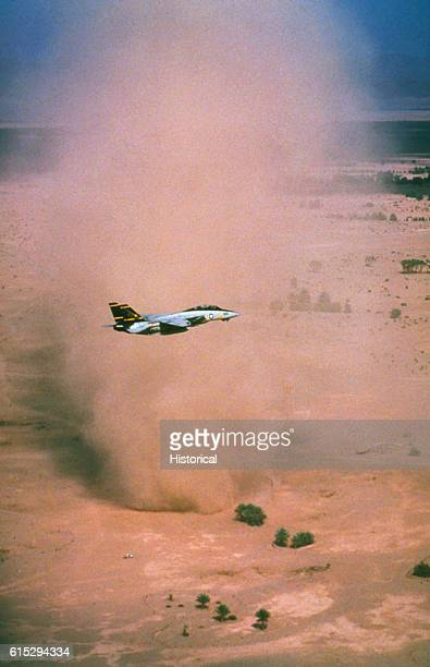 A Fighter Squadron 32 F14A Tomcat aircraft passes a desert dust storm during a flight off of the aircraft carrier USS John F Kennedy The Kennedy and...