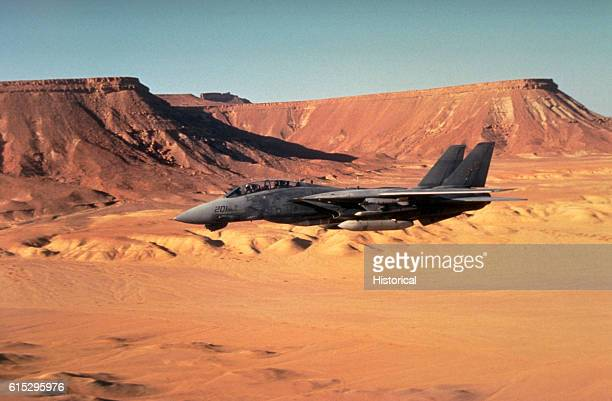 A Fighter Squadron 32 F14A Tomcat aircraft passes over the desert while on combat patrol off the aircraft carrier USS John F Kennedy during Operation...