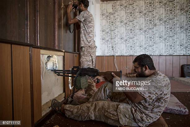 A fighter supporter of Libya's Tripolibased Government of National Accord fires his weapon from a liberated building on the frontline against the...