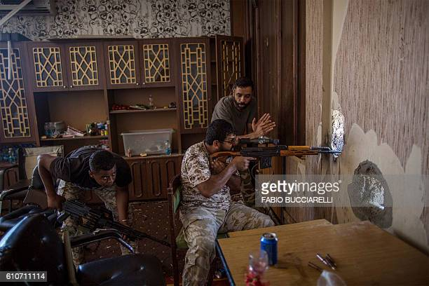 TOPSHOT A fighter supporter of Libya's Tripolibased Government of National Accord fires his weapon from a liberated building on the frontline against...
