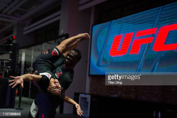 UFC fighter Uriah Hall lifts Jessica Andrade up after workout session during Fan Experience at UFC Performance Institute on June 21 2019 in Shanghai...