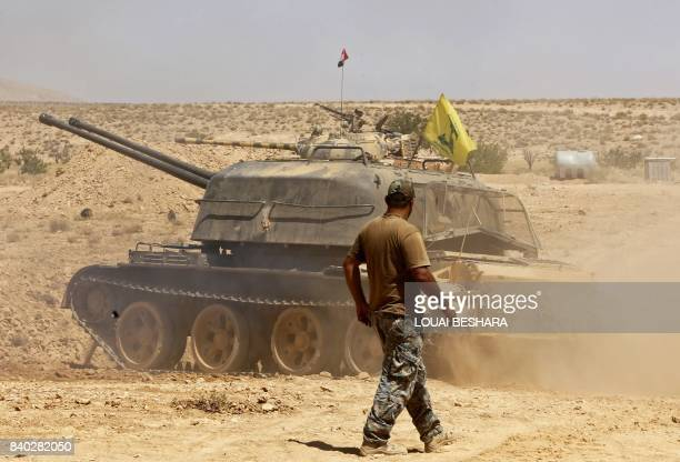 A fighter walks past a tank bearing a Hezbollah flag in the Qara area in Syria's Qalamoun region on August 28 2017 / AFP PHOTO / LOUAI BESHARA