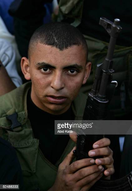 A fighter with the Al Aqsa Martyrs Brigades holds his weapon as he participates in a proelection rally March 28 2005 in the Beit Lahyea Refugee Camp...
