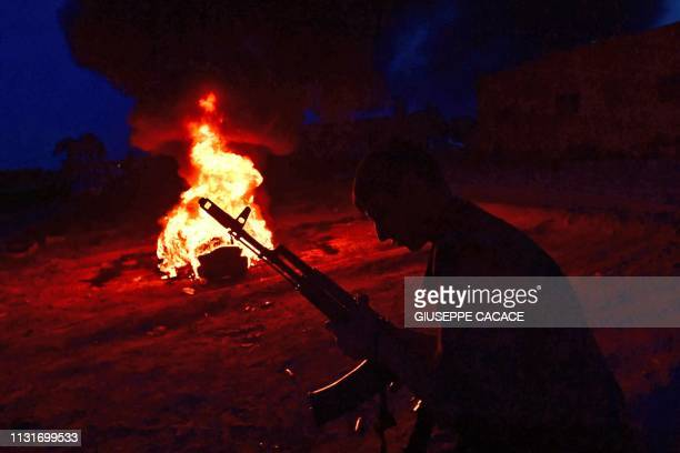 A fighter with the Kurdishled Syrian Democratic Forces stands in front of a bonfireduring Nowruz celebrations near the village of Baghouz in the...