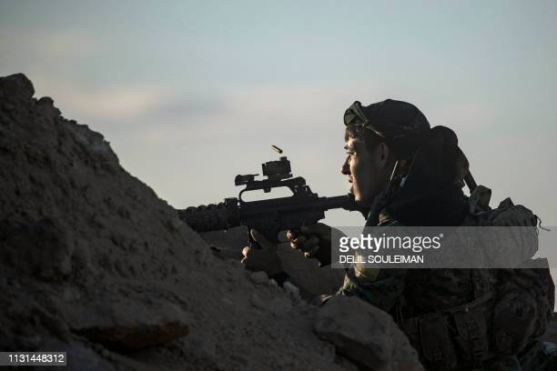 TOPSHOT A fighter with the Syrian Democratic Forces keeps position at a hilltop as he watches the Islamic State group's last remaining location in...