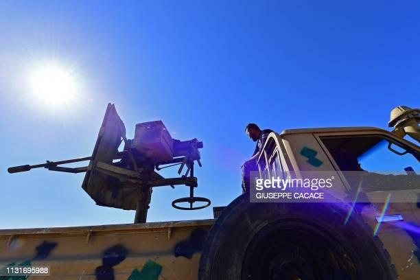 A fighter with the Syrian Democratic Forces sits atop a military vehicle near the village of Baghouz in the countryside of the eastern Syrian...