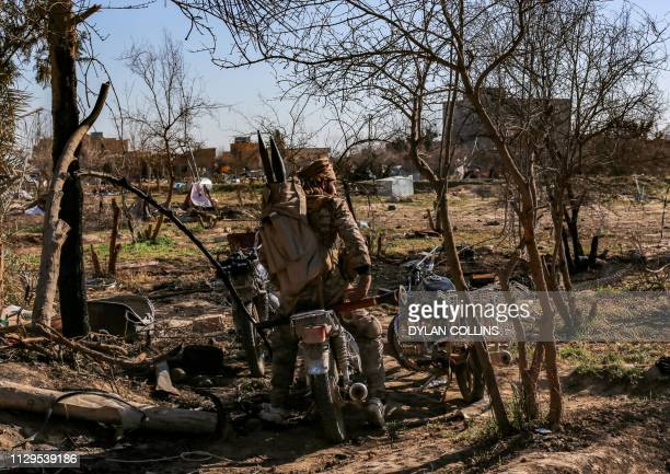 Fighter with the Syrian Democratic Forces sits on a motorcycle at a makeshift camp for Islamic State group members and their families in the town of...
